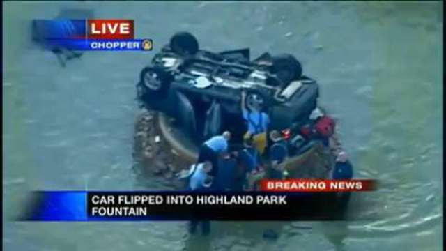 Vehicle overturned on top of fountain spout at Highland Park