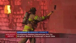 Firefighters putting out hot spots after huge warehouse fire