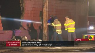 Firefighters work through the night after fire rips through warehouse