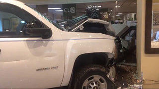 PHOTOS: Crash into furniture store sends truck driver to hospital