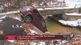 SUV crashes into creek behind thrift store, resting on front bumper
