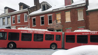 PAT bus with 15 passengers strikes row house after sliding on ice