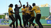 PITTSBURGH, PA - JUNE 23: Kevin Newman #27 of the Pittsburgh Pirates is mobbed by teammates after drawing a bases loaded walk off walk in the eleventh inning during the game against the San Diego Padres at PNC Park (Photo by Justin Berl/Getty Images)