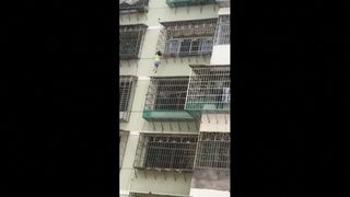 Girl dangles from fifth-floor window until rescued